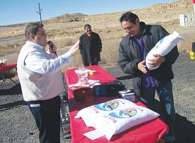 <i>Tyler Tawahongva/NHO</i><br> Cellular One District Supervisor Ethan Sewell (left) congratulates the winner of a sack of flour at a public celebration held Feb. 10 in Kykotsmovi.
