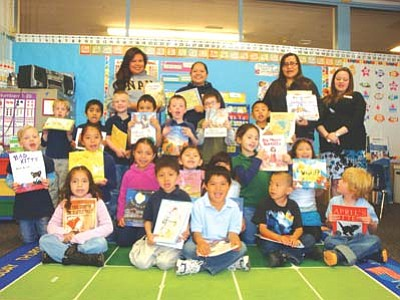 <i>Courtesy photo</i><br> Mrs. Salina Kinlicheeny and her kindergarten class show off their new books donated by NAU Gates Millenium Scholars on March 28.