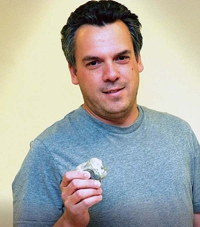 <i>Todd Roth/NHO</i><br> Bill Parker holding a petrified vertebra during his April 22 lecture in Winslow.