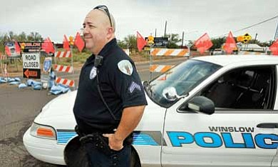 Todd Roth/NHO<br> Winslow Police Department Cpl. Ernie Canto assists travelers coming to Winslow from SR 87 south. BNSF SR 87 underpass is closed north and south at Winslow. Officer Canto is also providing quick response to any emergency arising in the southern part of Winslow