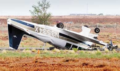 Todd Roth/NHO<br> An airplane remains upside down after crashing July 17 at the Winslow Lindbergh Regional Airport.