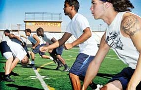 "Todd Roth/NHO<br> Players ""rush the punter"" in a drill during football camp at Winslow High School on July 22."