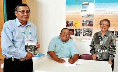 Submitted photo<br> Malcolm Benally (sitting) signs a book for Navajo Nation President Ben Shellley andFirst Lady Martha Shelley in Window Rock, Arizona.