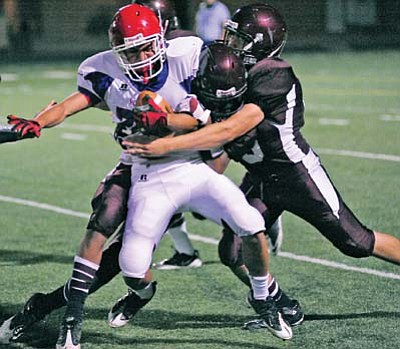 Todd Roth/NHO<br> Two Winslow Bulldogs take down a Holbrook player in a key play of the game.