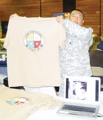"Rosanda Suetopka Thayer/NHO<br> Staff Sgt. LeRoy Outah, Arizona National Guard and member of the newly ""renamed"" Lori Piestewa Post No. 80, holds up a new shirt being sold and featured by the Hopi Veterans Post. The shirts are available for purchase either by phone or email. Pfc. Lori Piestewa was an enrolled member of the Hopi Tribe who became a national Native military icon in March 2003 when she was killed by Iraqi enemy fire in Nasiriyah along with several members of her 507th Maintenance Company."