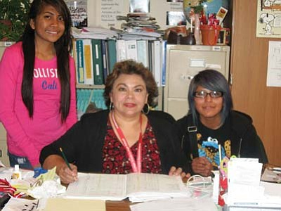 Submitted photo<br> Maria Goatcher sits at her desk with two students after finding out the high school had won the award.