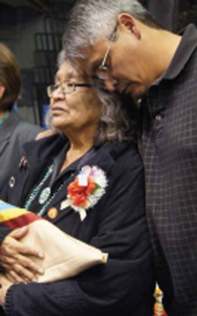 Submitted Photo<br> Eddie Little embraces his mother Nellie Little after she received the Navajo Nation flag from President Shelly.