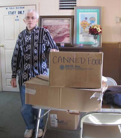 Submited Photo<br> Paul Gibson, who volunteers at the Grants Community Outreach Center in Grants, N.M., poses with boxes filled with donated non-perishable food delivered by staff members of the Navajo Nation Human Rights Commission.
