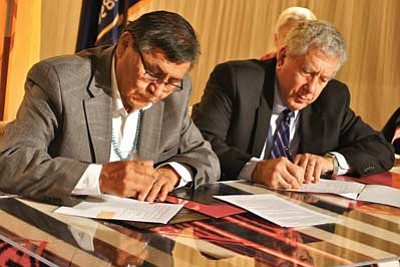 Submitted Photo<br> President Shelly and Ronald Cochran, LLNL executive, jointly sign a memorandum of understanding to help initiate energy development.