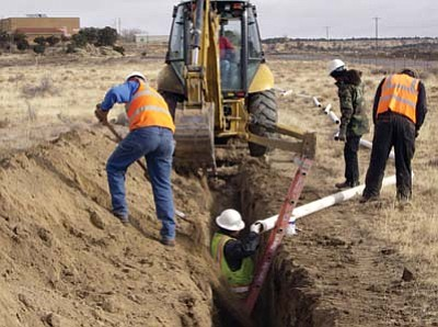 Photo/Rick Abasta<br> Workers dig a trench in order to install water line that will reach many Navajo families in need.