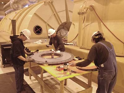 "Photo/George Hardeen<br> From left to right, Mitchell Emerson, Myron Whitehorse and Durral Whitehorse clean a section of the ""T-8"" bearing oil deflector by hand. This is a critical part of the Navajo Generating Station Unit 3 turbine behind them. They are among some 800 skilled workers involved in this year's four-week-long, $16 million annual minor overhaul."