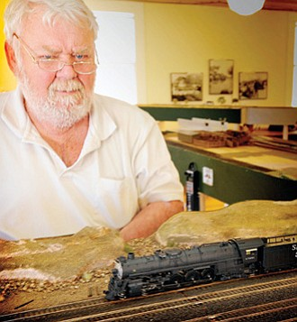 """Paul Thompson from """"Glendale FEMO"""" explains details of the model train layout at the Hubbell Center on April 20."""