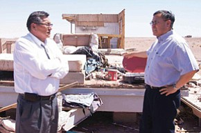 President Shelly (left) consults with Navajo-Hopi Land Commission Director Raymond Maxx about expediting funding for 17 families needing new homes. Behind this is the remainder of a single-wide trailer that was destroyed by a windstorm a few years ago.