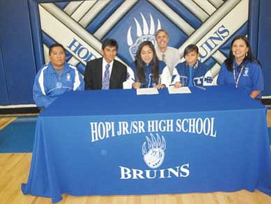 Hopi High girls cross country runners sign to attend Scottsdale Community College. They are, from left, Hopi High Athletic Director Wallace Youvella Jr., Scottsdale Coach Bo Reed, runners Lucinda Tungovia, Jasmine Humetewa and Hopi High Coach Laverne Lomakema. Hopi High Principal Glenn Gilman is in the background. <i>Stan Bindell/NHO</i>