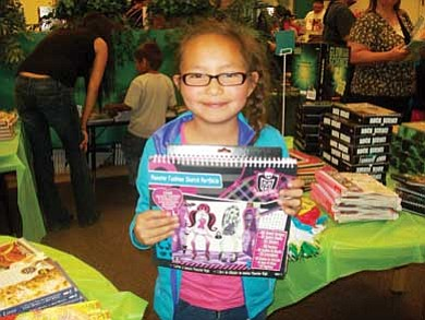 First grade student Hannah Yazzie smiles with delight as she selects a book from the Scholastic BOGO Book Fair at Indian Wells Elementary School. <i>Submitted photo</i>