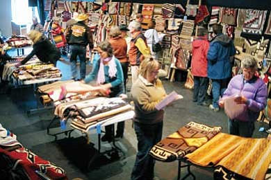 Shoppers peruse Navajo rugs prior to a previous auction. Submitted photo