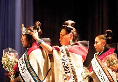 The new Miss Hopi, Jacqueline Poleahla, left, is crowned by out-going Miss Hopi, April Pavinyama, while first-runner Christine Talayumptewa looks on. The 2012 Miss Hopi Pagent took place on July 27, 2012, in Keams Canyon, Ariz.'s Hopi Jr./Sr. High School. Diego James Robles