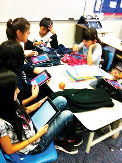 Students utilize iPads during an interactive learning program. Submitted photo