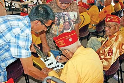 Shonie De La Rosa gets his custom made Navatone guitar signed by a Navajo Code Talker during National Code Talkers Day in Window Rock on Aug. 14. <i>Submitted photo</i>