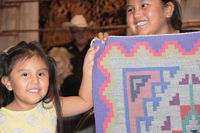 Volunteers show rugs to Navajo Rug Auction attendees during last year's event held at the Museum of Northern Arizona. Photo/Michele Mountain<br /><br /><!-- 1upcrlf2 --><br /><br /><!-- 1upcrlf2 -->