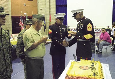 Sgt. Major Johnson cuts a 237th Marine Corp birthday cake with his Marine sword and serves the first pieces of cake to the oldest and youngest Marines in attendance, U.S. Marine Corps veteran Sgt. Floyd Honwaima (left) and U.S. Marine Corps Corporal Mack Talashie (right). Photo/Rosanda Suetopka Thayer