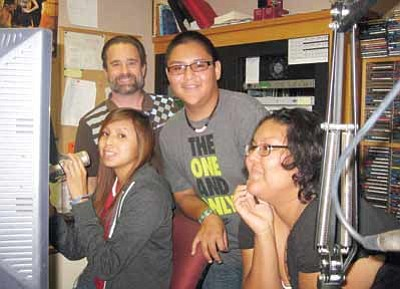 "KAFF/KMGN radio personality Charlie Hicks shows Hopi High students Sacheen ""Shano"" Mike, Detroit James and Lacey Tewanema how the station's radio computer works during a visit Nov. 29. Photo/Stan Bindell"