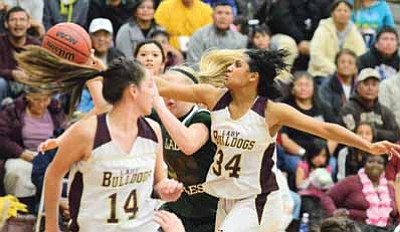 Halle Hayes fights for the ball as Marcella Joe looks on during the Winslow Lady Bulldog's loss to the Flagstaff Eagles Jan. 18. Photo/Todd Roth