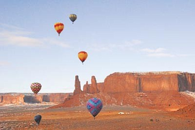 Balloons soar high above Monument Valley near the Three Sisters rock formation during the third annual Monument Valley Balloon Event Jan. 13. Photo/Geraldine Camarillo