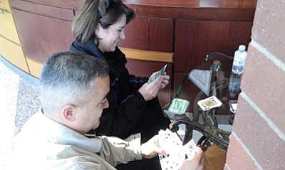 Leo Duran and Deanna Smith pass the time playing poker while waiting for an interview at the Twin Arrows Navajo Casino job fair Feb. 1. Photo/Gary Elthie
