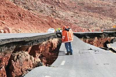 Arizona Department of Transportation employees survey damage to US 89 south of Page. The damage occurred Feb. 20. More than 500 feet of pavement is damaged likely because of a geologic slump. Photo/ADOT
