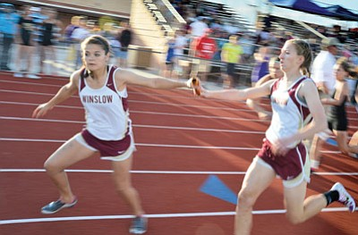 Winslow High School girls track team runners pass the baton during a relay event at the 81st annual Arizona Track Invitational April 26. Photo/Todd Roth