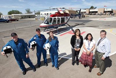 From left: Shawn Henrie, pilot, Andrew Armand, flight paramedic, Susan Stefano, flight nurse, Delores Succo, supervisory clinical nurse at Tuba City Regional Health Care Corporation (TCRHCC), Lynette Bonar, TCRHCC chief operations officer, and TCRHCC CEO Joseph Engelken  stand in front of the Angel 7 medical helicopter based in Tuba City. Photo/Flagstaff Medical Center