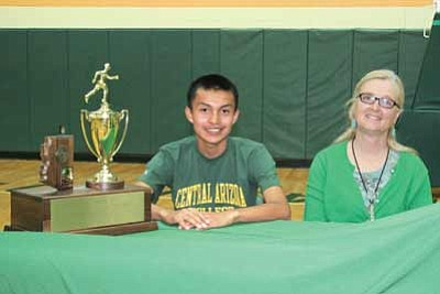 Shawn Tsinnijinne, 2013 Tuba City High School Cross Country and Track Athlete of the Year and Athlete of the Year will attend Central Arizona College in the fall of 2013 on a cross country scholarship. Tsinnijinnie sits with Karin Jones, acting Tuba City High School principal and the state cross country school trophy in Warrior Pavilion. Photo/Rosanda Suetopka Thayer