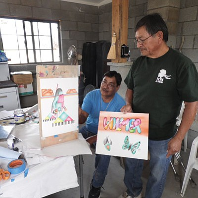Hopitutuqaiki Art School Master Instructor Anthony Honahnie (right) displays some basic first week instruction examples that student Wilmer Kaye (seated) created during Honahnie's  air brushing art class. Photo/Rosanda Suetopka Thayer