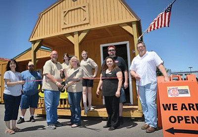 Graceland Portable Buildings' Mark and Kathy Strango (center) celebrate their grand opening at 700A Mikes Pike, Winslow. Photo/Todd Roth
