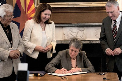 White Mountain Apache Chairman Ronnie Lupe, left, looks on as Interior Secretary Sally Jewell signs a water-rights agreement with the tribe. Also on hand were Rep. Ann Kirkpatrick, D-Flagstaff, and former Arizona Sen. Jon Kyl.Photo by Evan Bell