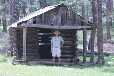 Dave Fickas enjoys the shade the Pinchot Cabin provides. The cabin was once part of a network of old fireguard cabins along the Mogollon Rim. Photo/Stan Bindell