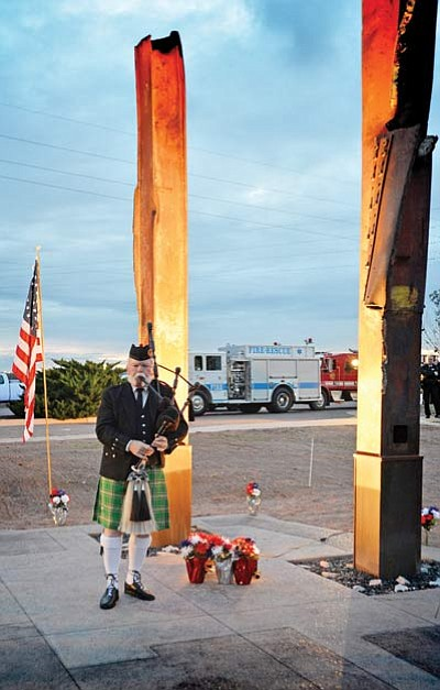 A bagpiper plays in front of columns from the destruction of the World Trade Center in 2001 during last year's memorial service in Winslow. Photo/Todd Roth