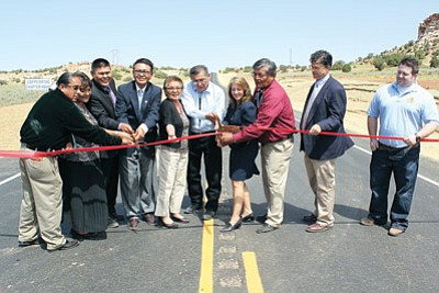 Oficially cutting the ribbon to the new roadway are from left: Darryl Tso, speaker's office; Lena Fowler, Coconino County supervisor, Paulson Chaco, Navajo Division of Transportation director; Duane Tsinigine, Navajo Nation Council delegate; First Lady Martha Shelly; Navajo Nation President Ben Shelly; Karla Petty, Federal Highway Administration Division administrator; Floyd Stevens, Coppermine Chapter president; Robert Samour, Arizona Department of Transportation senior deputy state engineer and Ammon Heier, FHWA area engineer. Photo/Rick Abasta