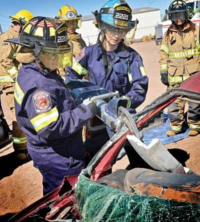 Two Joseph City Emergency Responders cut into an auto windshield pillar during an Oct. 5 Winslow emergency response training. Photo/Todd Roth