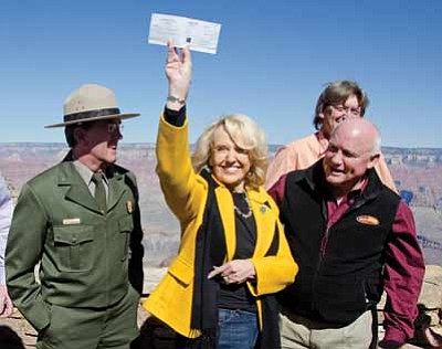 Arizona Governor Jan Brewer holds a check for $426,500 presented to her by the town of Tusayan. Left: Grand Canyon National Park Superintendent Dave Uberuaga; right: Mayor Greg Bryan and councilmember Craig Sanderson. Photo/NPS