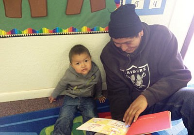 A Hopi father reads to a young boy. The Hopi Lavayi Nest Model Program aims to connect children in Hopi communities to their native language and culture in the critical early years. Submitted photo