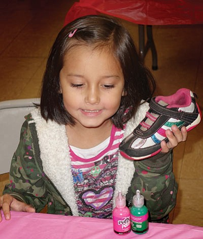 A young Winslow resident decorates her shoe at Kicking Kancer Winslow Oct. 10. Photo/Todd Roth