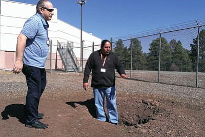 Kelvin Long, a Navajo who will serve as cultural adviser for a Native American religious program at the Coconino County Jail, and Jim Bret, program coordinator for detention services, look over the site of a  fire pit that will be outside a sweat lodge planned for the jail. About half of the inmates are Native American. Cronkite News Service Photo by Andrew Knochel