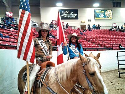 Flag bearers are waiting for the opening ceremony to start.  Sonyah Clifford, Oglala Sioux and Miss Indian Rodeo, holds the U.S. flag and Eugenia Kirk, Navajo, of New Town, N.D., holds the Canadian flag as they wait for the opening ceremony to begin. Kirk is one of eight candidates vying for the next Miss Indian Rodeo title. Photos/Gary Elthie