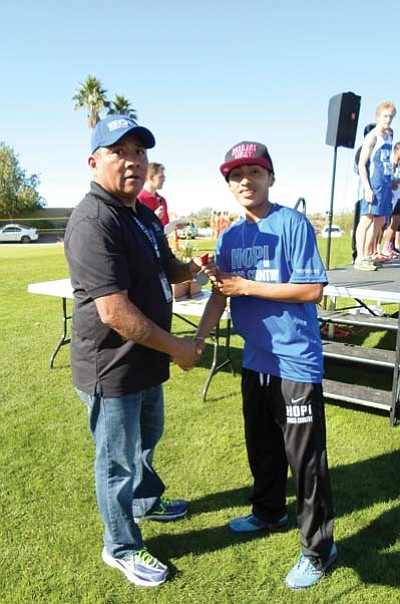 Arizona Interscholastic Association official Wallace Youvella Jr. presents a medal to Anfernee Howard for finishing second in the race. Photo/Stan Bindell