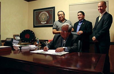 Speaker of the Navajo Nation Council Johnny Naize signs legislation in his office.