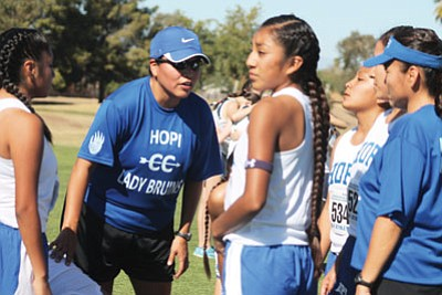 Hopi High Coach LaVerne Lomakema gives her runners pointers. Photo/Stan Bindell
