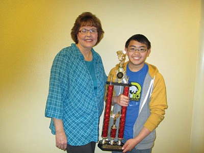 Hopi Junior High's Sean Bolus displays his Navajo County Spelling Bee first place trophy next to his spelling bee advisor Rita Keith. Photo/Stan Bindell