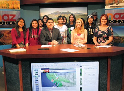 Hopi High School media students stand behind Northern Arizona University television personalities on NAZ TV's set Feb. 27. Photo/Stan Bindell
